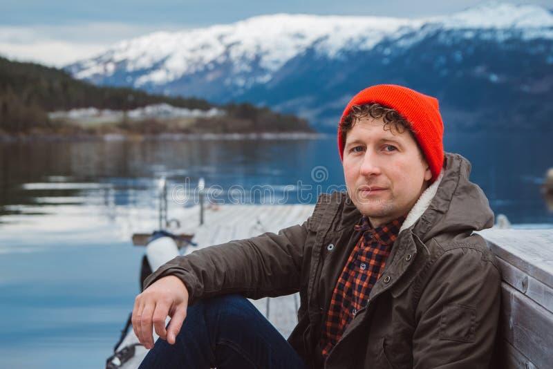 Hombre del viajero del retrato que lleva un sombrero rojo que se sienta en el embarcadero de madera en el fondo de la monta?a y d fotografía de archivo