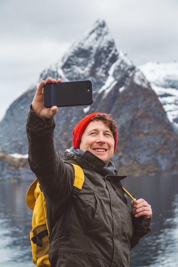 Hombre del viajero del retrato que toma a autorretrato una foto con un smartphone Turista en una situaci?n amarilla de la mochila imágenes de archivo libres de regalías