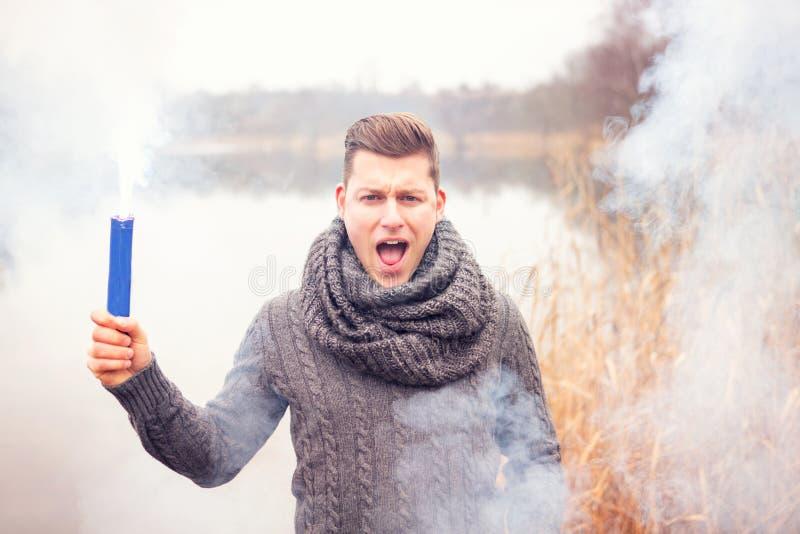 Hombre delante del lago que sostiene una antorcha que fuma foto de archivo