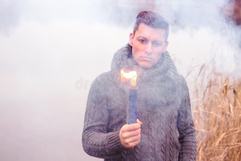 Hombre delante del lago que sostiene una antorcha que fuma imagen de archivo libre de regalías