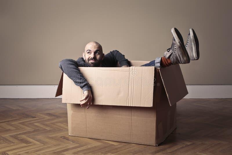 Hombre dentro de una caja de cartón imagenes de archivo