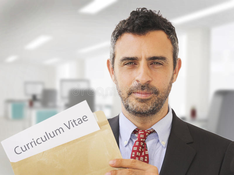 Hombre dentro de una oficina que sostiene los papeles del CV imagen de archivo