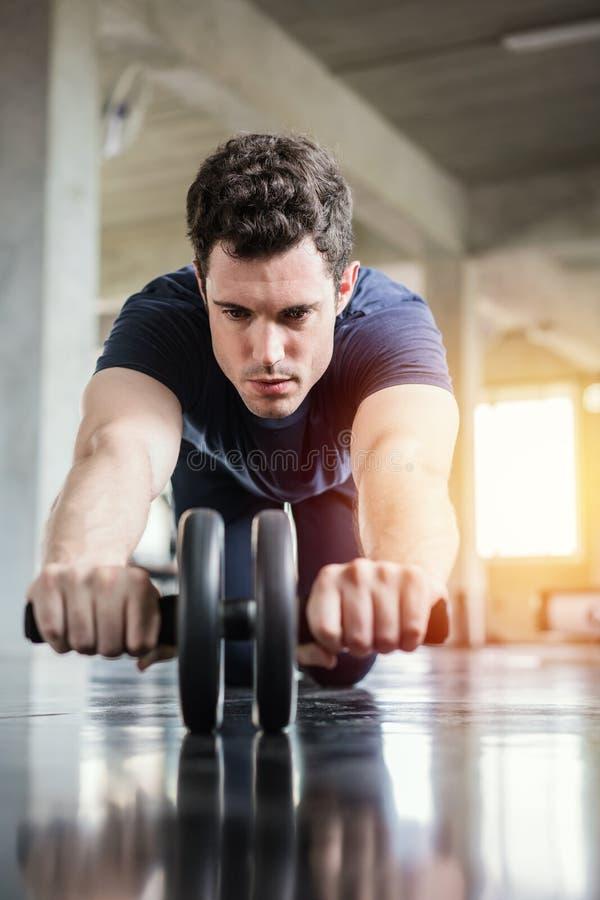 Hombre deportivo del atleta que hace ejercicio con la rueda del rodillo del ABS para fortalecer su m?sculo abdominal en gimnasio imagen de archivo