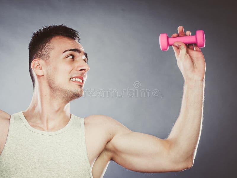 Hombre deportivo divertido del ajuste que levanta pesa de gimnasia ligera Diversión imagen de archivo libre de regalías