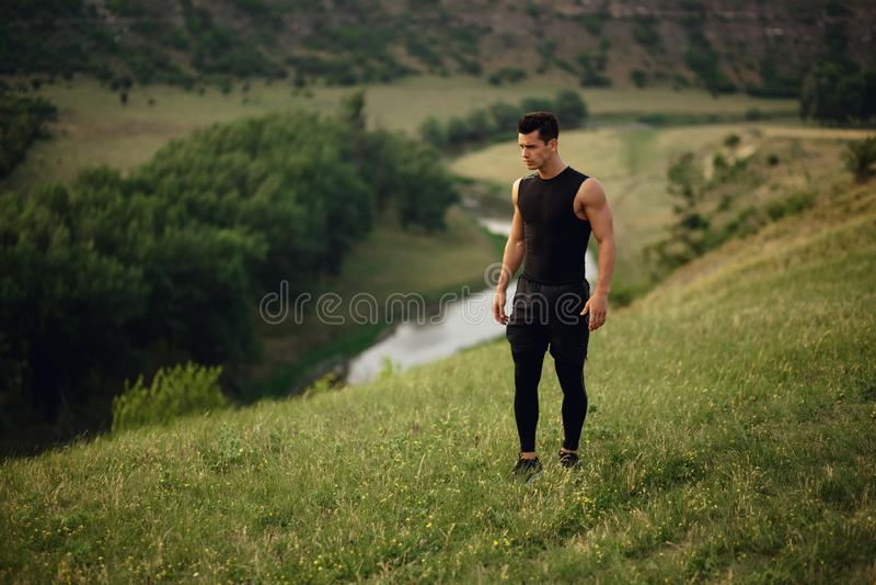 Hombre deportivo en entrenamiento de la ropa de deportes afuera, aislado en un fondo hermoso del paisaje imagen de archivo libre de regalías