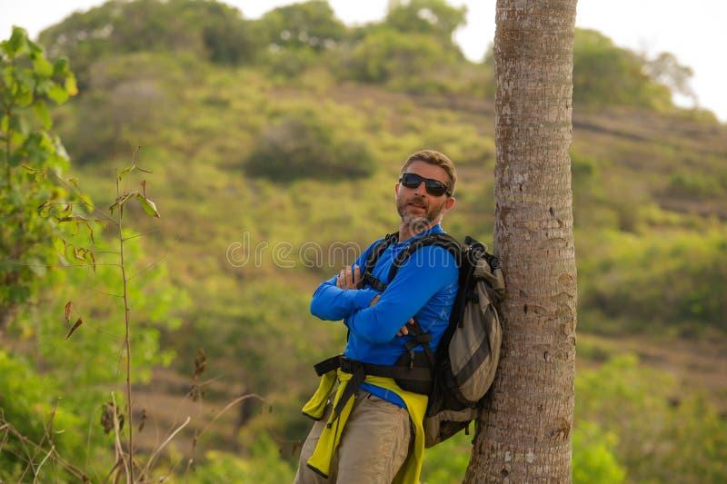 Hombre deportivo feliz y atractivo joven del caminante con emigrar la mochila que camina en la partida de goce libre del viaje de imagen de archivo libre de regalías
