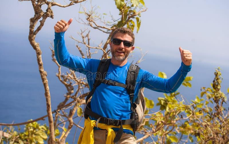 Hombre deportivo feliz y atractivo joven del caminante con emigrar la mochila que camina en la partida de goce libre del viaje de fotografía de archivo libre de regalías