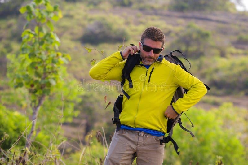 Hombre deportivo feliz y atractivo joven del caminante con emigrar la mochila que camina en la partida de goce libre del viaje de fotos de archivo