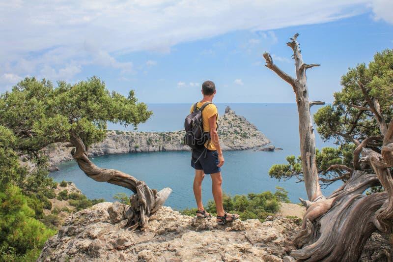 Hombre deportivo joven con la mochila que se coloca en el top de la roca fotografía de archivo libre de regalías
