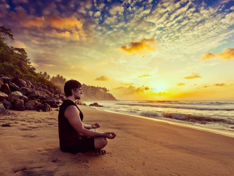 Hombre deportivo joven del ajuste que hace la yoga que reflexiona sobre la playa tropical fotos de archivo libres de regalías