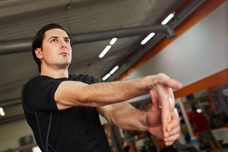 Hombre deportivo joven en el sportwear negro que estira el brazo antes de entrenamiento del gimnasio imagen de archivo