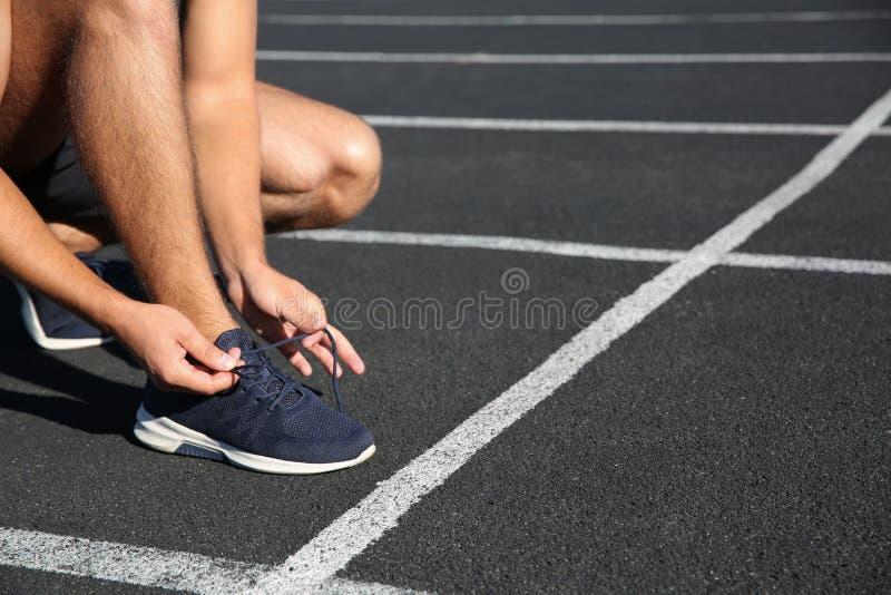 Hombre deportivo que ata cordones antes de correr en el estadio en mañana soleada fotos de archivo libres de regalías