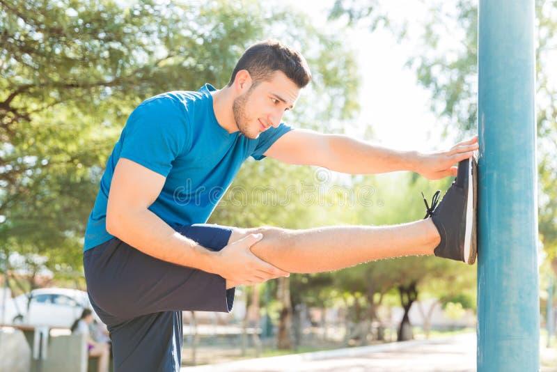 Hombre deportivo que estira la pierna y el brazo en poste en parque fotografía de archivo libre de regalías