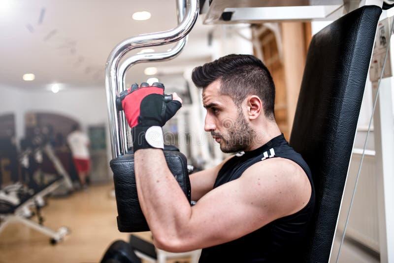 Hombre deportivo que hace ejercicio del pecho en el gimnasio imagen de archivo libre de regalías