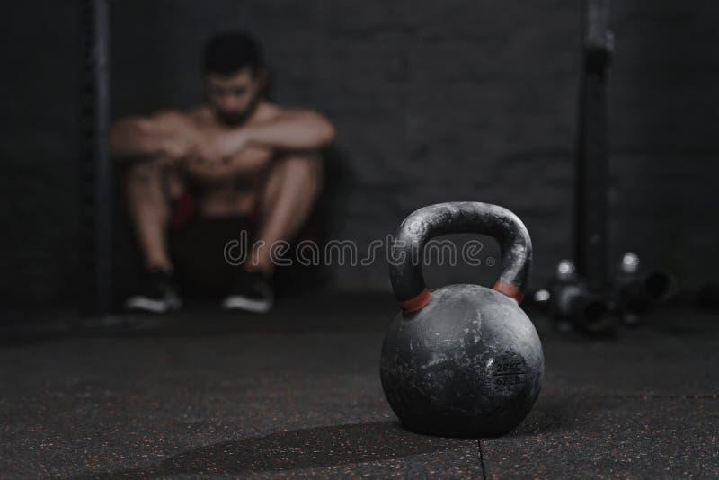 Hombre deportivo que se sienta en la avería del sufrimiento del gimnasio para superar Concepto del deporte de la desmotivación Te fotografía de archivo libre de regalías
