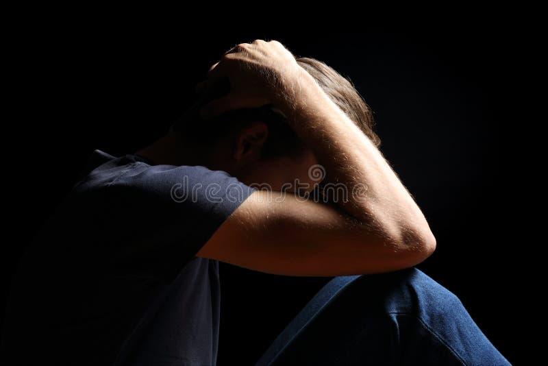 Hombre deprimido del adolescente en negro foto de archivo