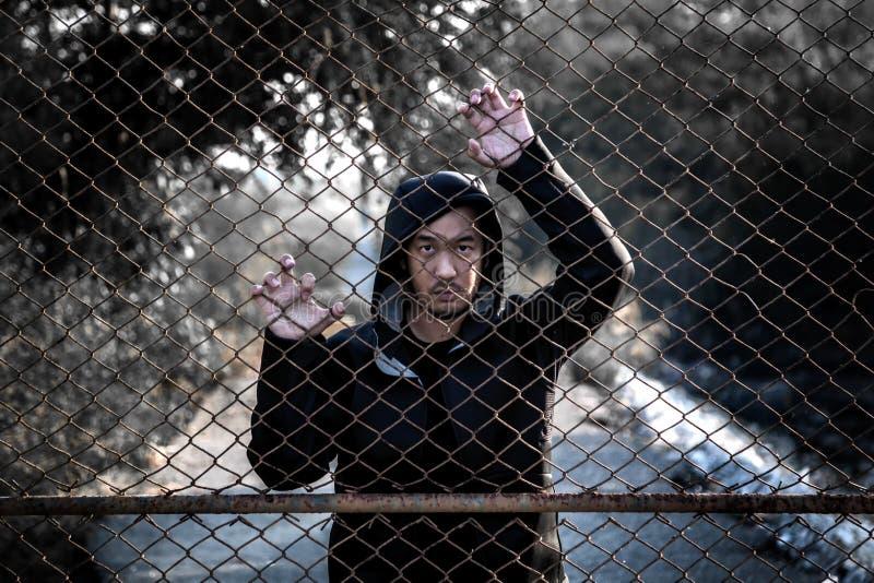 Hombre deprimido que lleva una sudadera con capucha negra que se coloca detrás de una cerca Han fotografía de archivo libre de regalías