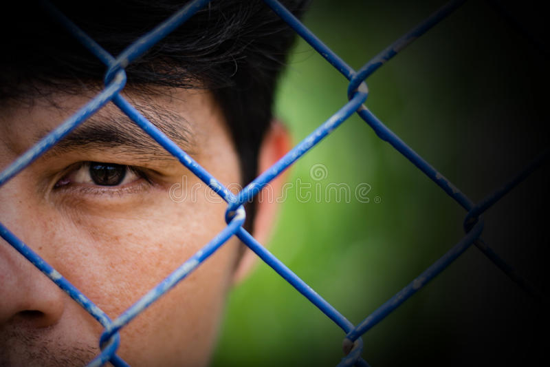 Hombre deprimido que se coloca detrás de una cerca, cierre para arriba en cara foto de archivo