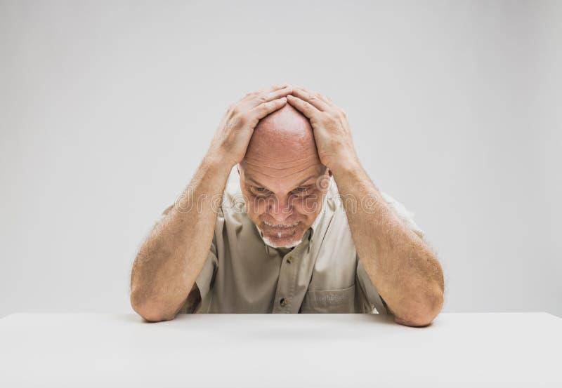 Hombre deprimido que se sienta en la tabla imágenes de archivo libres de regalías