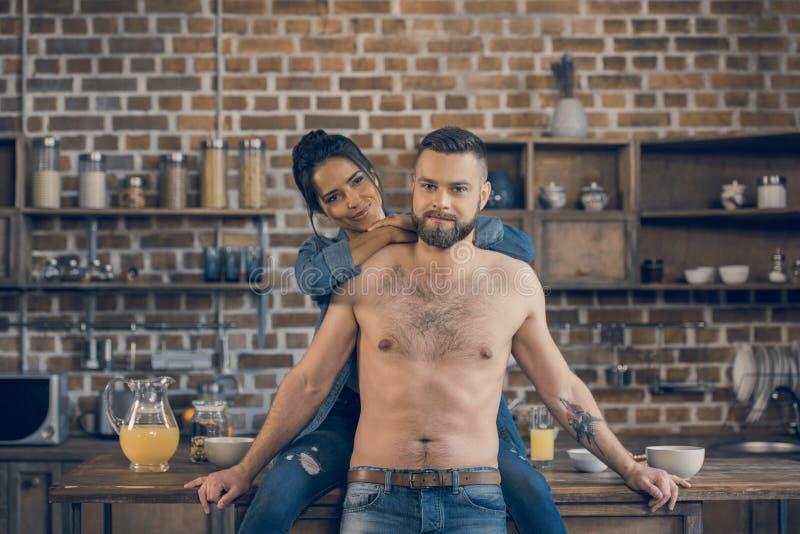 Hombre descamisado barbudo y su novia que abrazan en cocina fotos de archivo