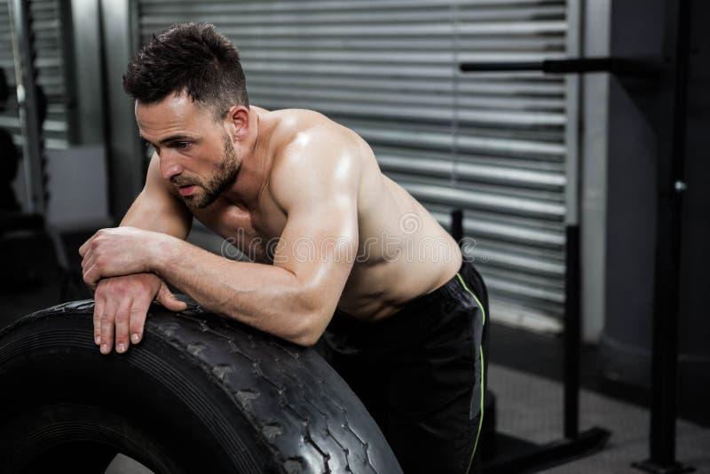 Hombre descamisado cansado que se inclina contra el neumático pesado fotos de archivo
