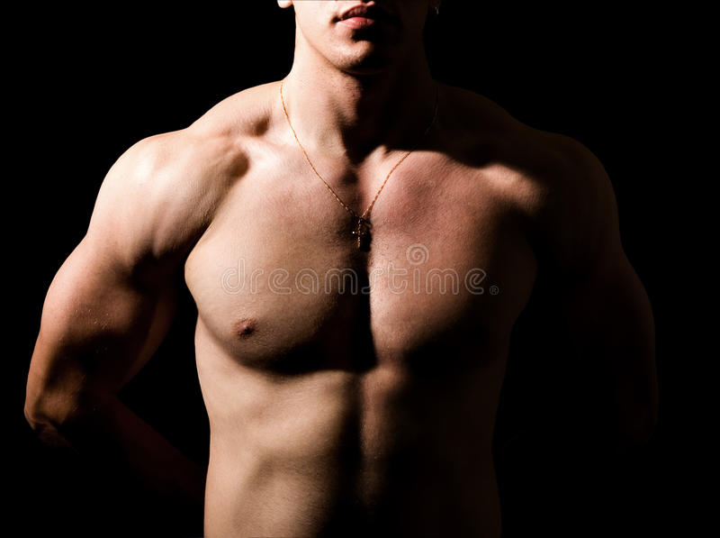 Hombre descamisado con la carrocería atractiva muscular en la obscuridad foto de archivo libre de regalías