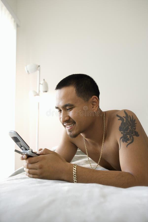 Hombre descamisado en cama usando el teléfono celular. imágenes de archivo libres de regalías
