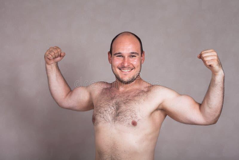 Hombre descamisado feliz que plantea y que muestra su cuerpo fuerte fotos de archivo