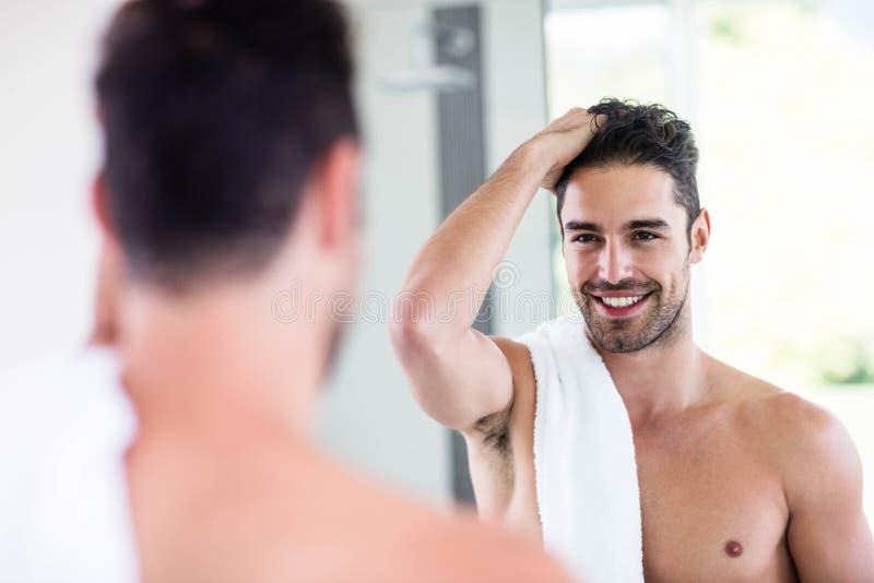 Hombre descamisado hermoso que mira en el espejo imagen de archivo libre de regalías