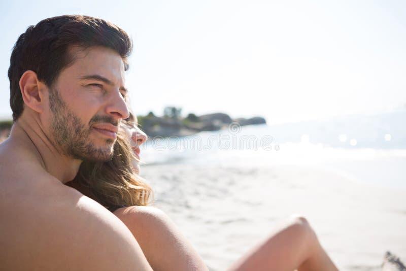 Hombre descamisado joven pensativo con su novia que se sienta en la playa fotos de archivo