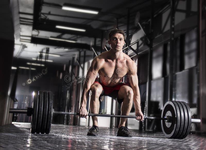 Hombre descamisado joven que hace ejercicio del deadlift en el gimnasio imagen de archivo