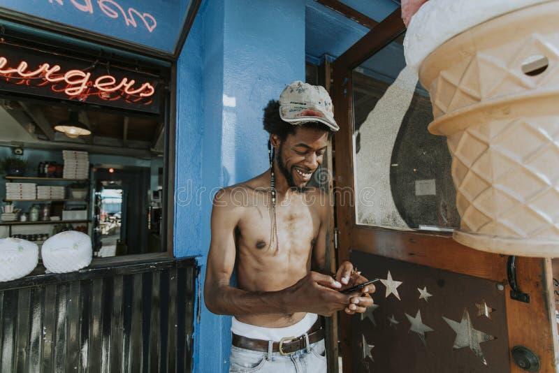 Hombre descamisado que juega en su teléfono fuera de un restaurante imágenes de archivo libres de regalías