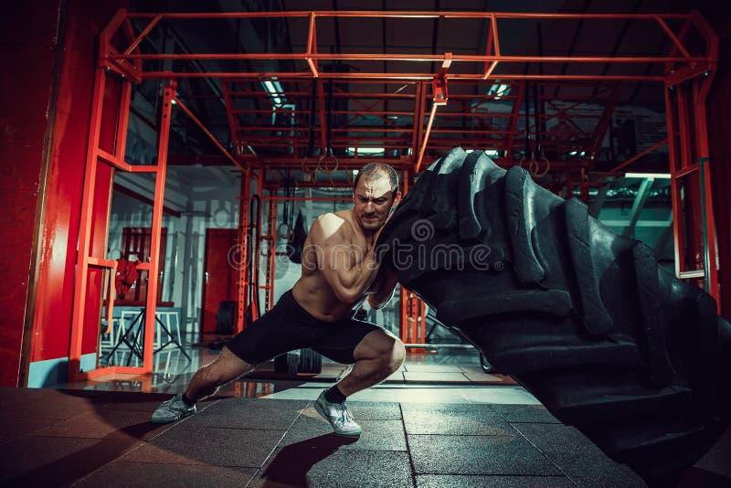 Hombre descamisado que mueve de un tirón el neumático pesado foto de archivo