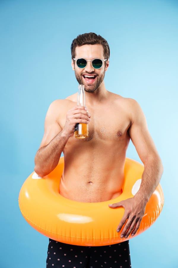 Hombre descamisado sonriente feliz que lleva el anillo inflable fotos de archivo