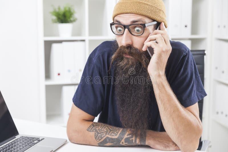 Hombre desconcertado con la barba larga en el teléfono foto de archivo