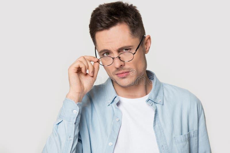 Hombre desconfiado del retrato principal del tiro que baja las lentes que miran la cámara fotografía de archivo