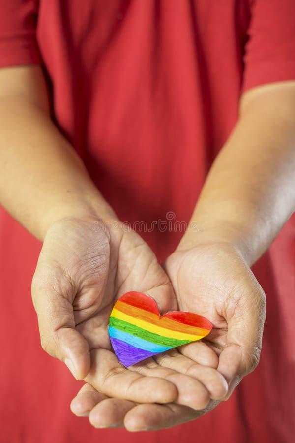 Hombre desconocido que muestra el corazón con color del arco iris imagen de archivo libre de regalías