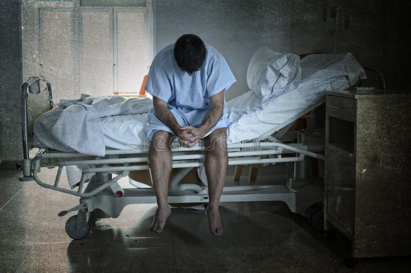 Hombre desesperado que se sienta en la cama de hospital solamente triste y la depresión sufridora devastada que llora en la clíni imagen de archivo libre de regalías