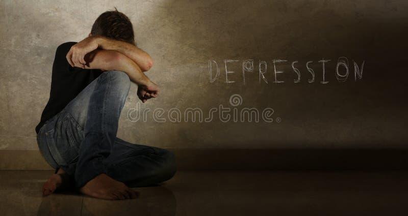 Hombre desesperado y deprimido joven que llora solamente con la depresión de la palabra escrita en la pared fotografía de archivo