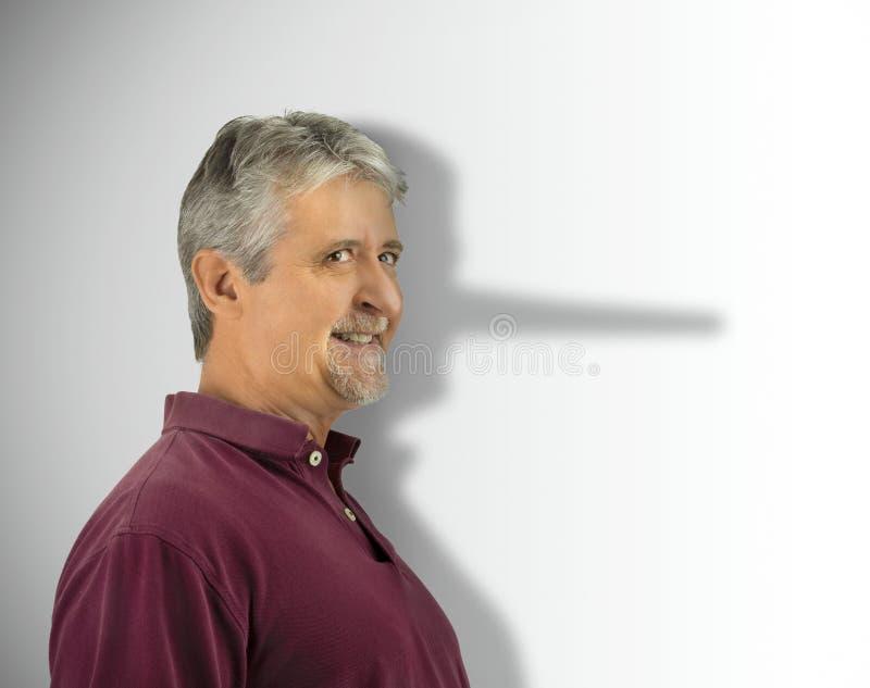 Hombre deshonesto de mentira con su nariz larga creciente de Pinocchio del mentiroso que muestra en su sombra fotografía de archivo libre de regalías