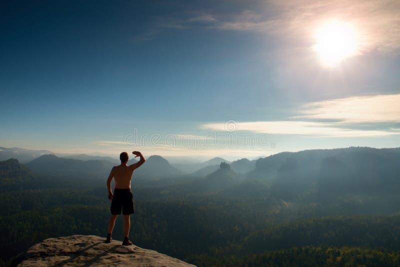 Hombre desnudo en pantalones negros solamente en la parte superior de la montaña en la puesta del sol foto de archivo