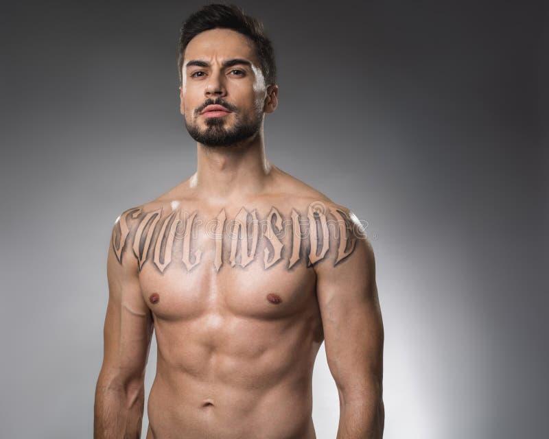 Hombre desnudo serio con el tatuaje fotografía de archivo