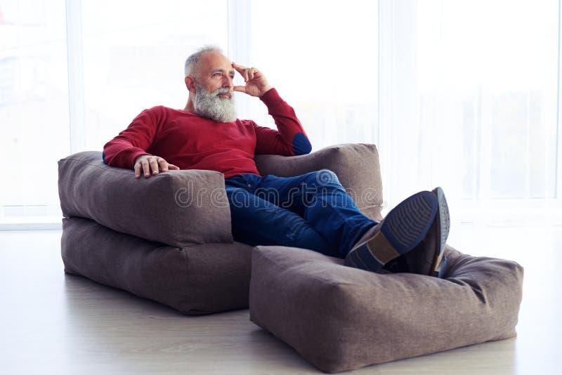 Hombre despreocupado que se relaja en butaca al lado de la ventana en casa fotos de archivo libres de regalías