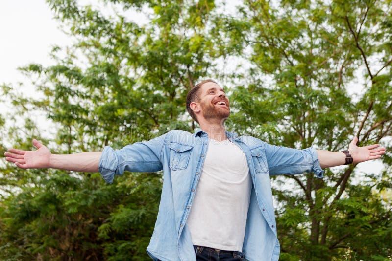Hombre despreocupado y libre que aumenta sus brazos foto de archivo