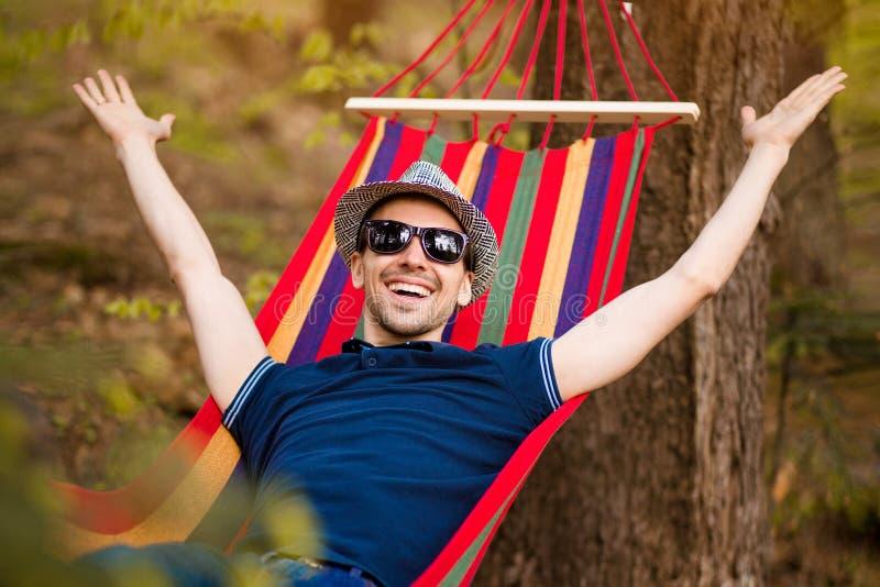 Hombre despreocupado y libre que aumenta sus brazos rodeados de resto del rato de la naturaleza del bosque en la hamaca fotografía de archivo