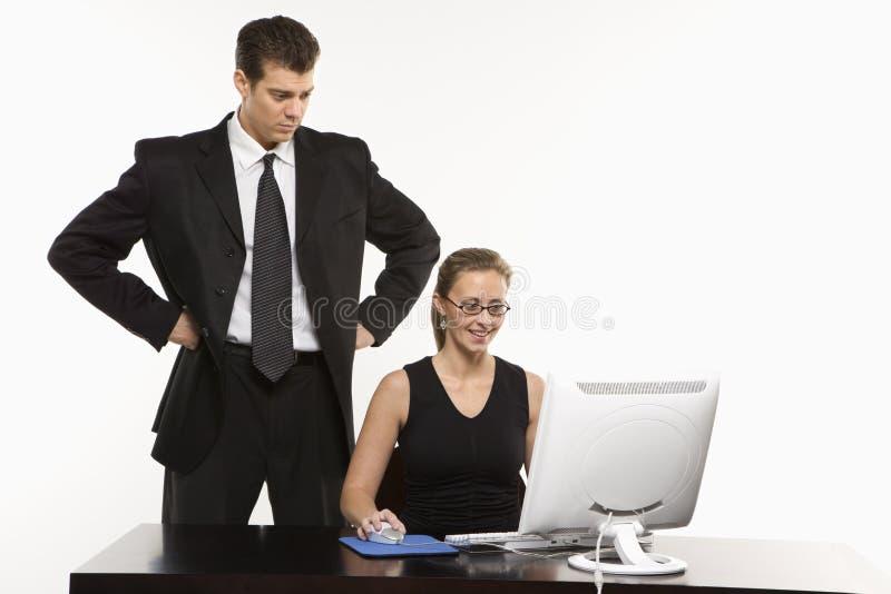 Hombre detrás de la mujer en el ordenador imagen de archivo