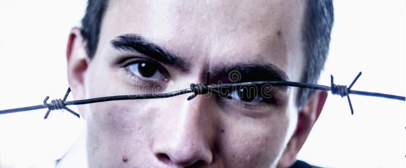 Hombre detrás de un alambre de púas como símbolo del dolor y de la desesperación Foco selectivo en el alambre de p?as foto de archivo