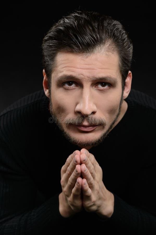 Hombre devoto que ruega. Hombre barbudo devoto que ruega y que lleva a cabo su h fotografía de archivo