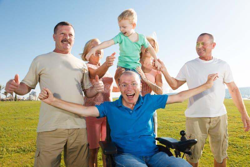 Hombre discapacitado con la familia imagen de archivo libre de regalías