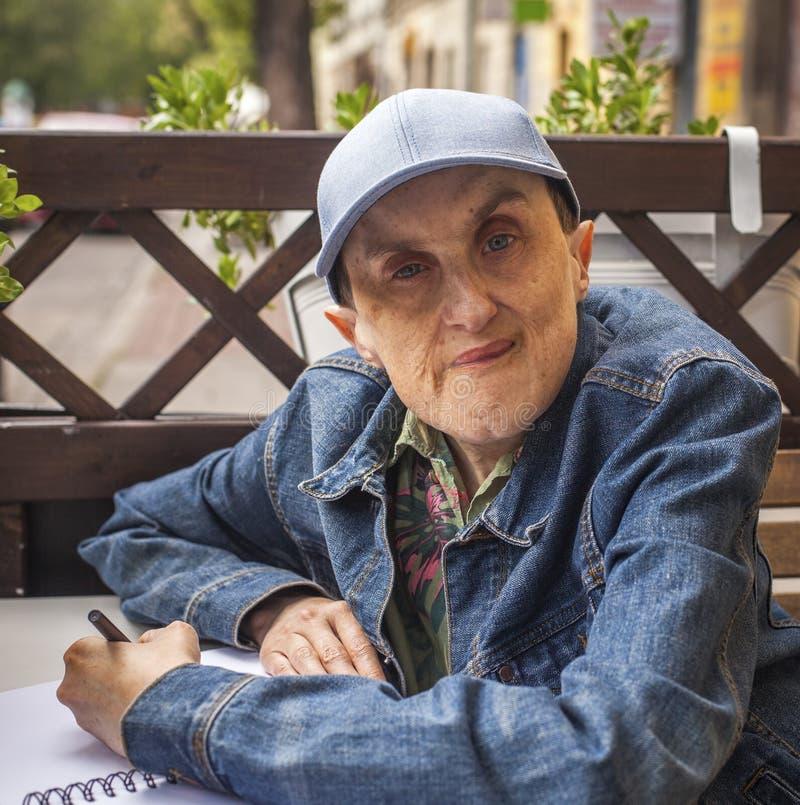 Hombre discapacitado con la parálisis cerebral que se sienta en el café al aire libre fotografía de archivo